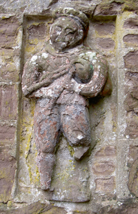 Carving of a piper, originally on a gate pillar at Ballinton, now built into a wall at Abercairney